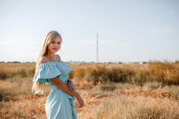 Young beautiful caucasian blonde girl in light blue dress stands
