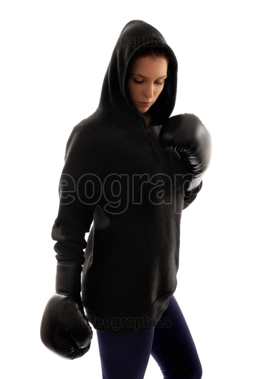 Young beautiful female boxer reflecting