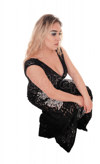 Young blond woman crouching on the floor in a black dress