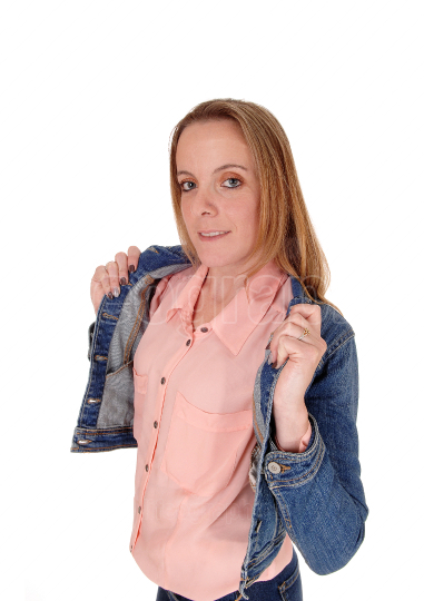 Young blond woman standing holding her jeans jacket