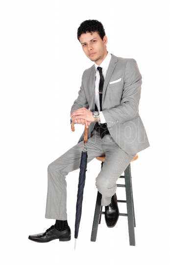 Young bossiness man sitting in a gray suit