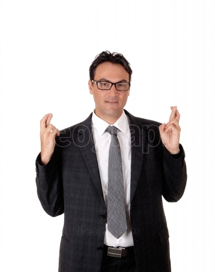 Young business man giving a sign with fingers crossed