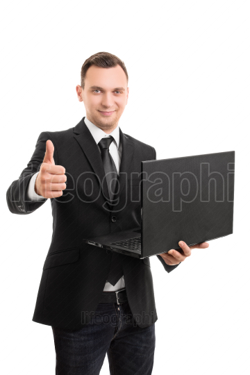 Young businessman holding a laptop giving a thumbs up