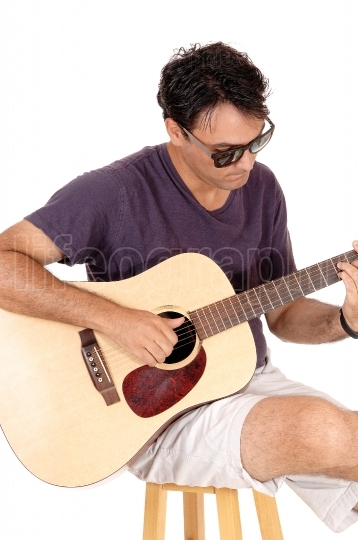 Young casual dressed man playing the guitar and sitting