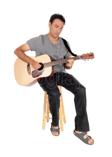 Young casual man playing the guitar