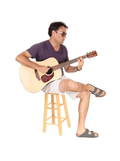 Young casual man playing the guitar and sitting