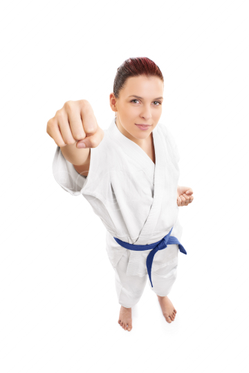 Young female aikido fighter attacking