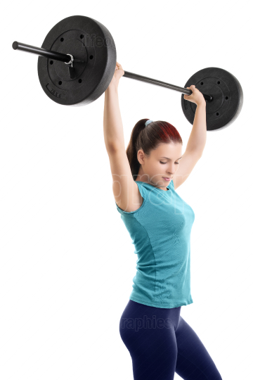 Young girl doing shoulder press with barbell