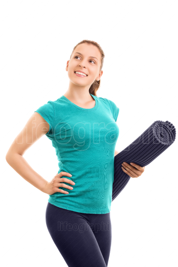 Young girl holding an exercise mat