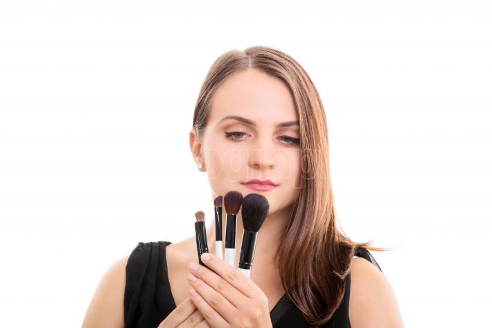 Young girl holding some make up brushes