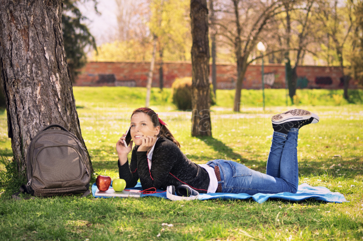 Young girl in a park talking on the phone