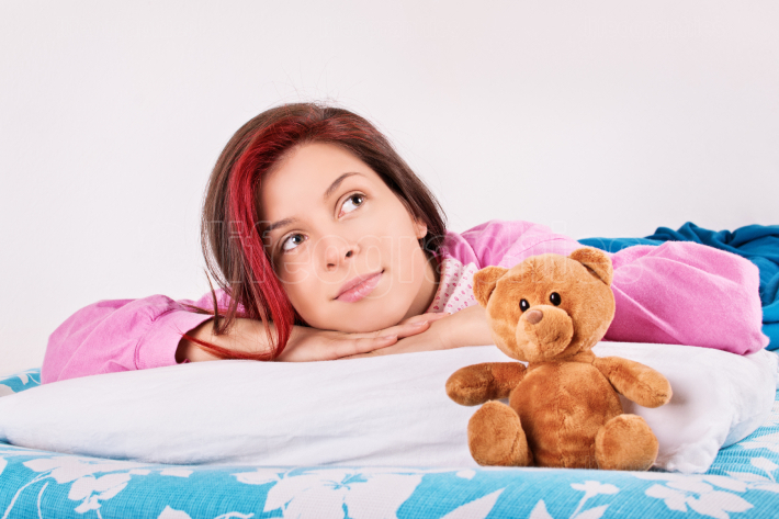 Young girl in bed with her teddy bear