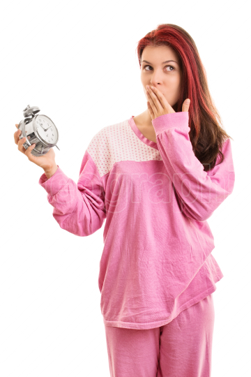 Young girl in pajamas holding an alarm clock