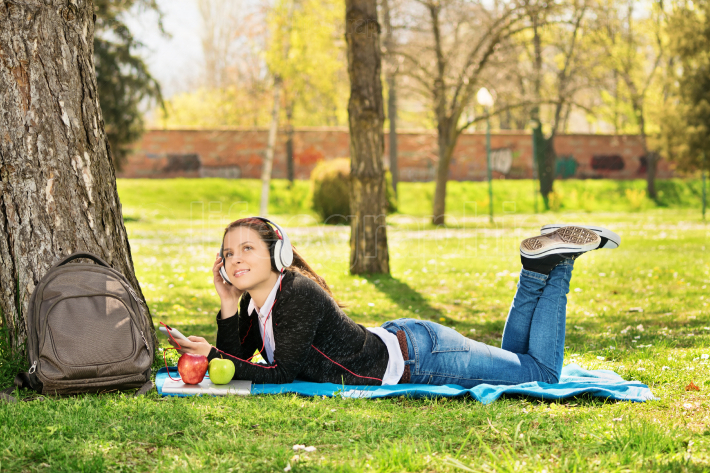 Young girl listening to music in the park