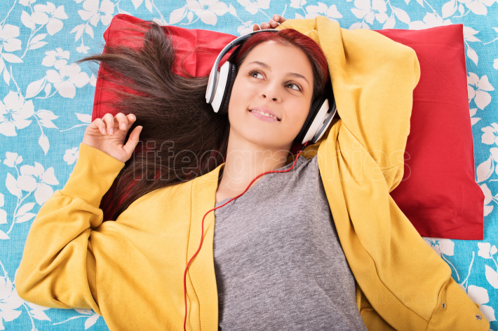 Young girl listening to music on her bed