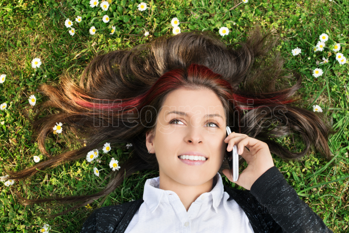Young girl lying on a meadow talking on the phone