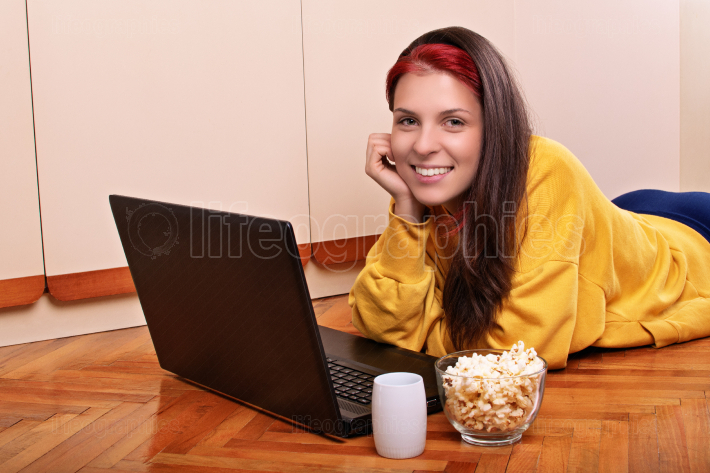 Young girl ready to watch a movie with popcorn and cup of warm d