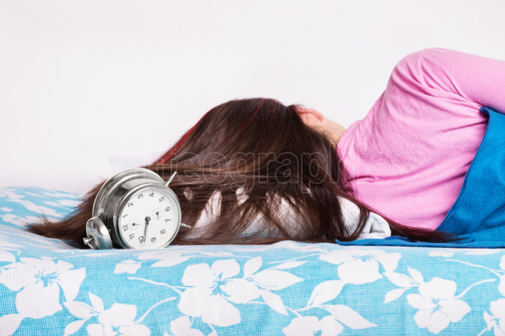 Young girl sleeping while the clock is ringing