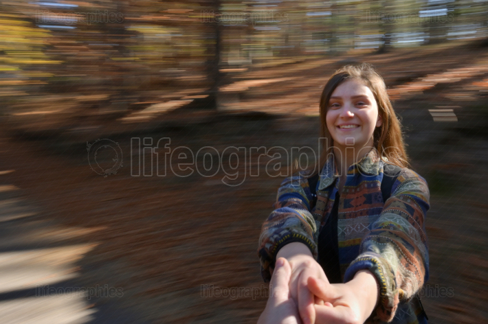 Young girl spinning in forest