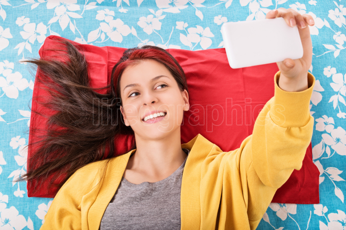 Young girl taking a selfie on her bed