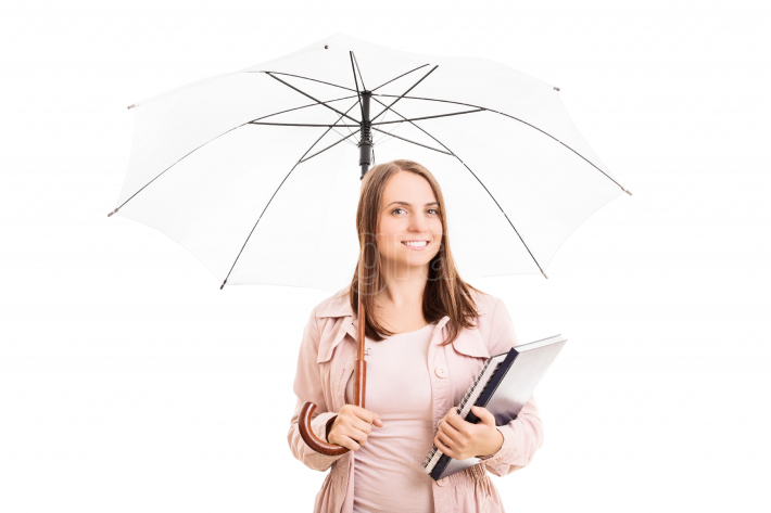 Young girl under an umbrella carrying some notebooks