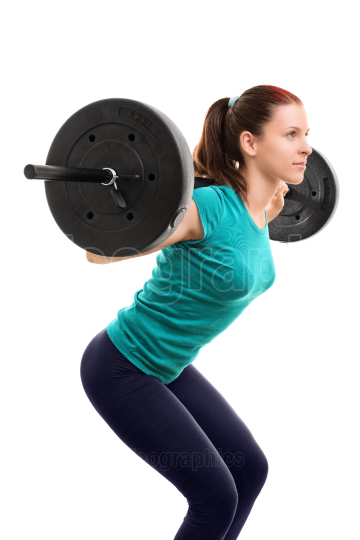 Young girl with a barbell doing squats