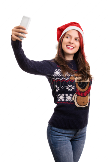 Young girl with a christmas hat taking a selfie