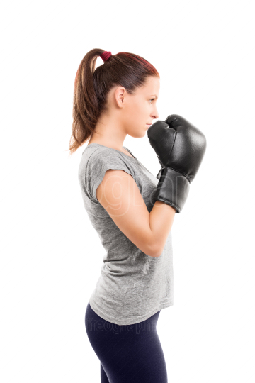 Young girl with boxing gloves holding her guard up