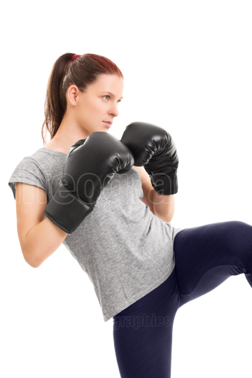 Young girl with boxing gloves ready to strike