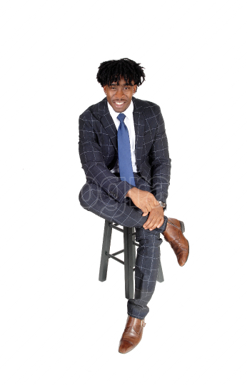 Young good looking black man sitting on chair in suit