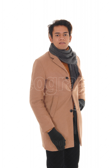 Young happy man in a beige winter coat and scarf