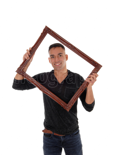 Young man holding up a picture frame and smiling