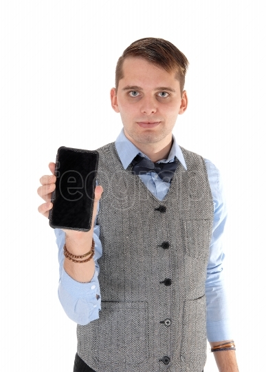 Young man holding up his cell phone in a vest