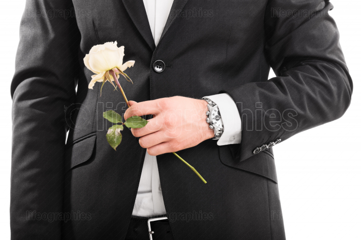 Young man in a suit holding a flower