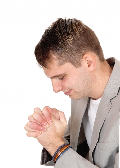Young man praying with hands folded