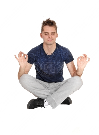 Young man sitting on floor in a yoga pose