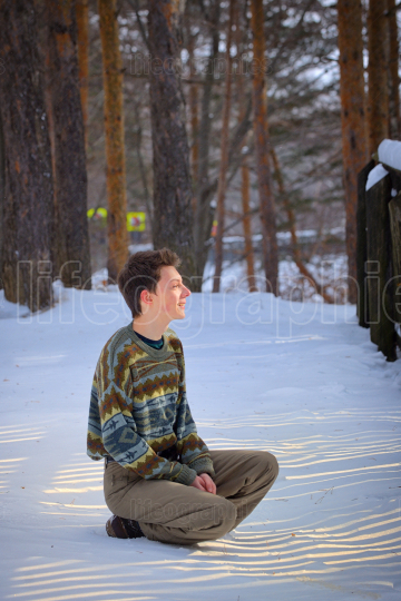 Young man sitting on snow