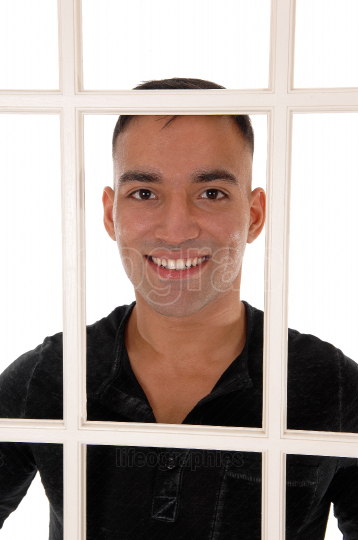 Young man smiling behind a white window frame