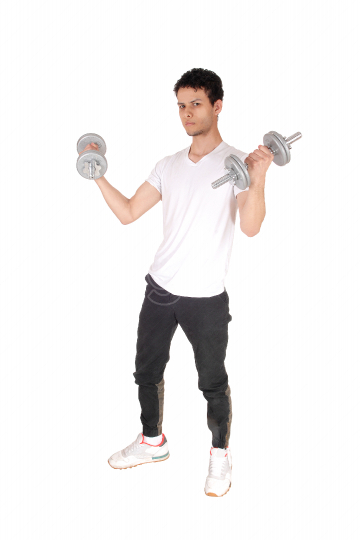 Young man standing and exercising with two dumbbells