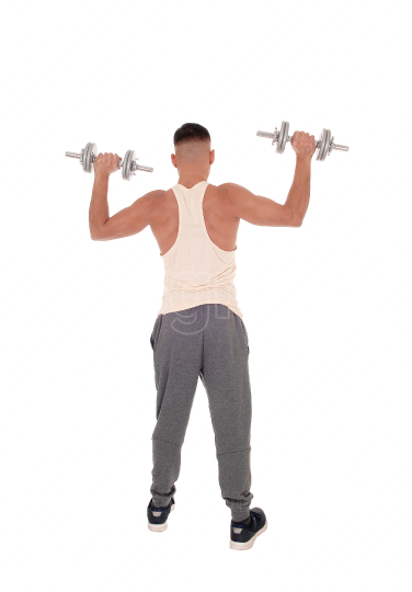 Young man standing from back with two dumbbells