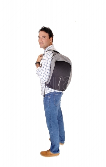 Young man standing in profile with his backpack
