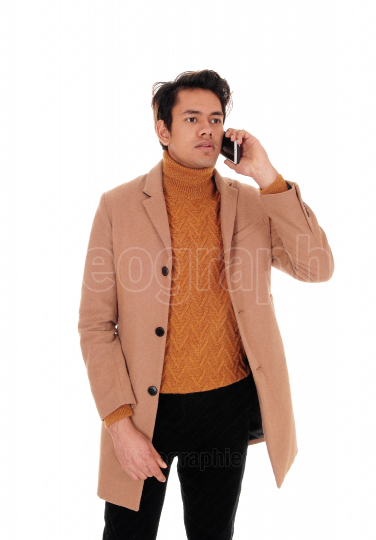 Young man talking on cell phone in a coat