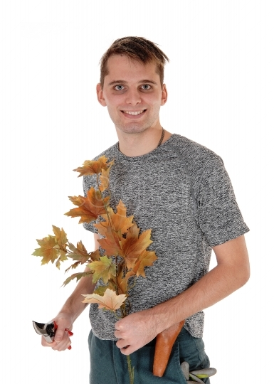 Young man working on autumn trees cutting