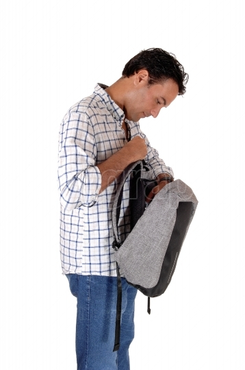 Young tall man looking into his backpack