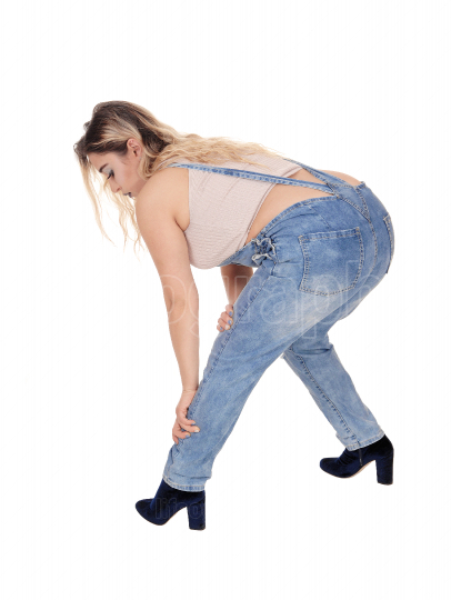 Young woman bending down in her jeans pants