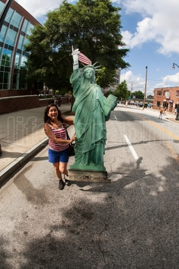 Young Woman Carries Cardboard Statue Of Liberty At Immigration Protest