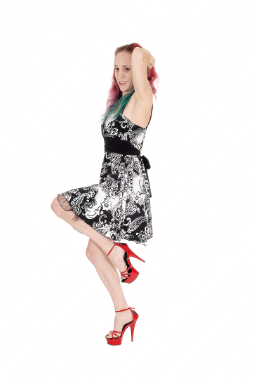 Young woman dancing in a dress and red heels