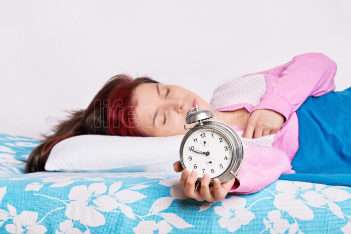 Young woman fallen asleep with alarm clock in hand