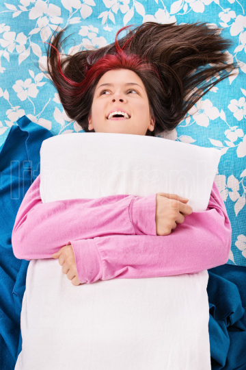 Young woman in bed smiling and hugging a pillow