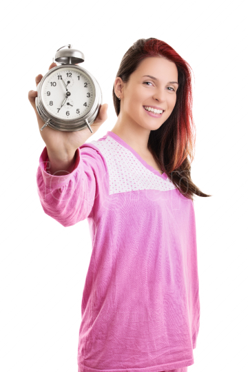 Young woman in pajamas holding alarm clock and smiling